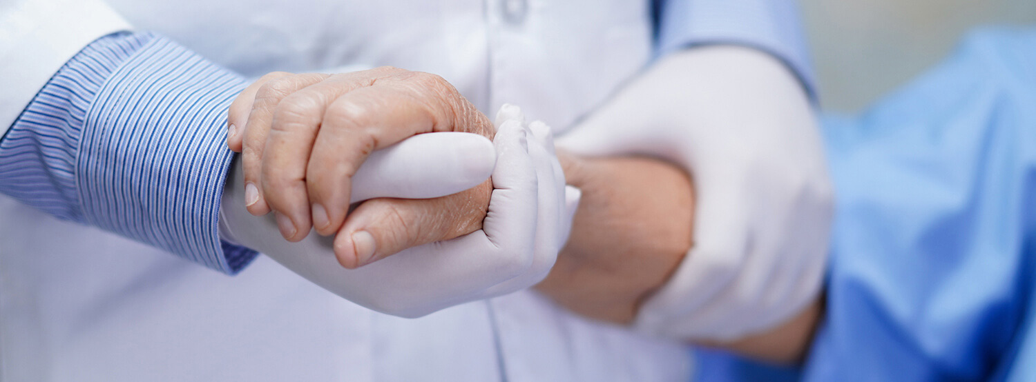 a doctors hand holding a patients hand
